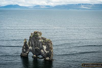 Hvítserkur rock, decorated by local birdlife, and Blönduós township across the fjord