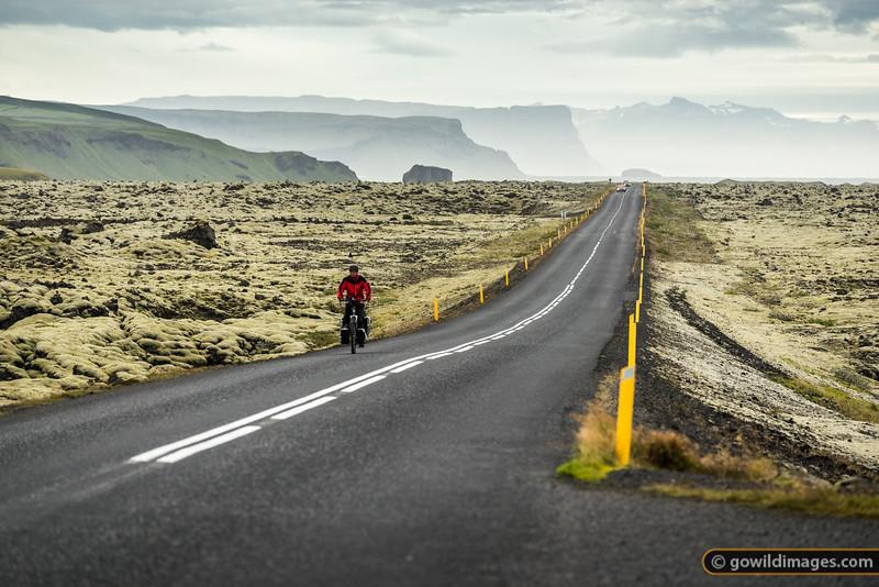 A cyclist cruises Road 1 East, towards Kirkjubæjarklaustur