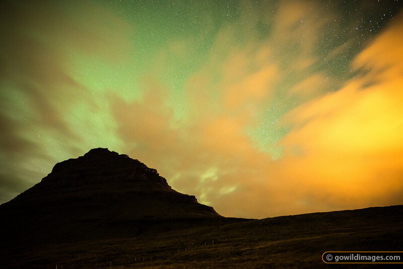 Kirkjufell (Church mountain) below a starry September sky. The clouds are illuminated by nearby Grundarfjordur, with the green glow due to a small display of Aurora Borealis - 'The Northern Lights'