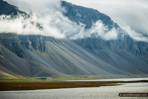 Sheep graze around Svínhólar farm beneath an ominous volcanic slope