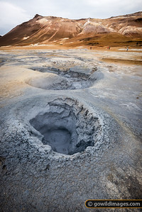 Boiling mud pot at Hverir geothermal area, Námafjall hill beyond
