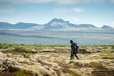 A diver heads back across an old lava field with 30kg of equipment at the end of the day. With hood, gloves, drysuit, insulation suit and thermals, you can remain pretty warm and dry for an hour or two in the near-freezing water.