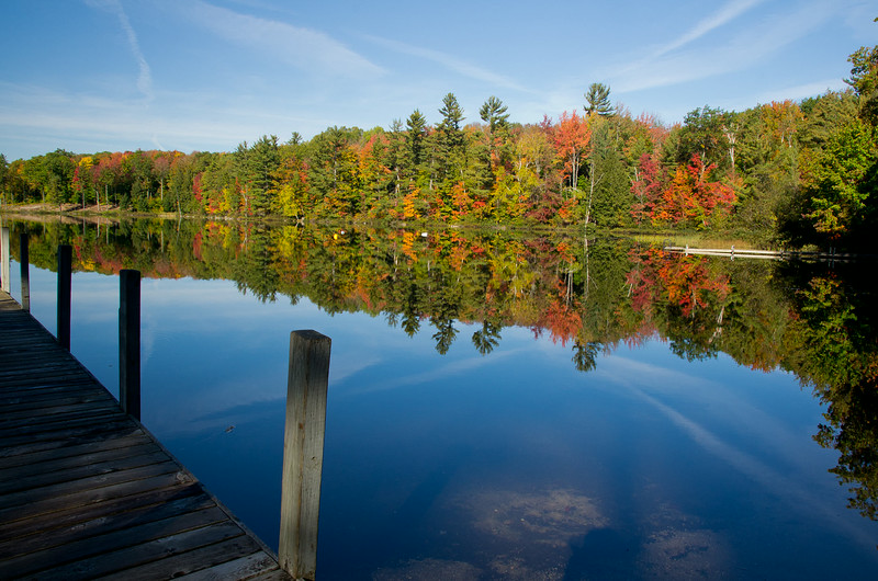 Fall colors are mirrored on Lake Hernendeen seen from the dock of Sleeping Bear Resort in Lake Ann, Michigan.