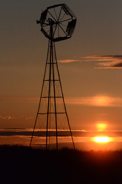 A modern windmill stands in a farmers field watching the sun come up