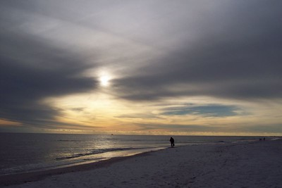Lone beach walker with a hole in the sky