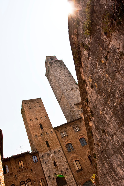 Several of the towers in San Gimignano framed by the steps of the church.