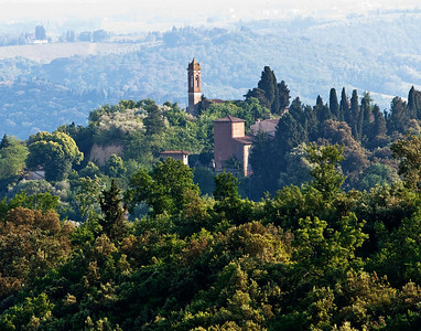 A beautiful tower and ancient looking buildings on a hill in Tuscany in the Chianti Region.