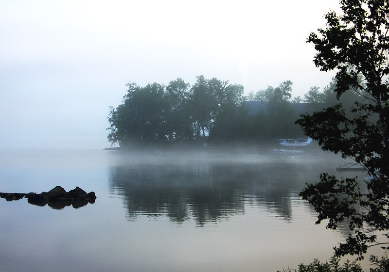 Soft morning mists on Moosehead Lake in Maine hide a small float plane