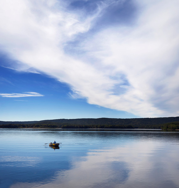 Man fishing in a row boat on Quabbin Reservoir New England Massachusetts