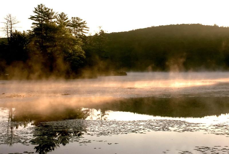 Morning mist at sunrise on Harvard Pond New England