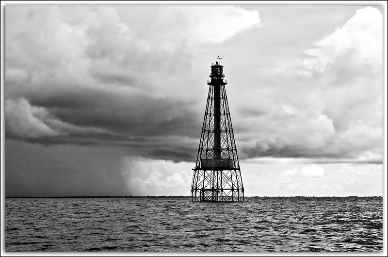 Sombrero Key Light off of Marathon in the Florida Keys. The solitary beacon has steadfastly withstood many storms such as this..and far worse since it was completed and lit by a first order Fresnel lens on March 17, 1858. In 2008 this light will have stood sentinel on Sombrero Shoal for 150 years.
