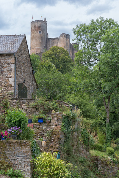 Medieval stone built house in Najac with Najac Castle in the background on an unsettled day in July