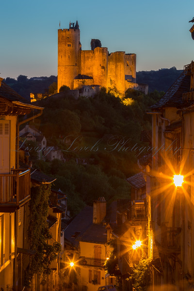 As night falls, the castle at Najac is illuminated to contrast against the sky.