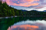 """""""Eibsee Sunset in the German Alps"""" Too often photographers are focused looking directly ahead at the big scene. This is one of those times when the scene BEHIND me was MUCH more exciting than a gigantic mountain right in front of me. While shooting sunset at the Eibsee Lake at the Zugspitze in the German Alps near Garmisch-Partenkirchen, the sunset behind me really started to come alive. I looked for the right composition and the curves of the lush green trees along the shore caught my eye. The subtle reflections in the water together with that symphonic feeling of the light concert above me. Wow.... what a feeling. Hopefully this captures some of that beauty to bring back to share. Lesson - Always turn around look around you! Even with a 10,000 foot mountain in front of you (which wasn't bad!), there might be other pictures around you. I'll keep this one. Let me know what YOU think!   — at Zugspitze in Germany"""