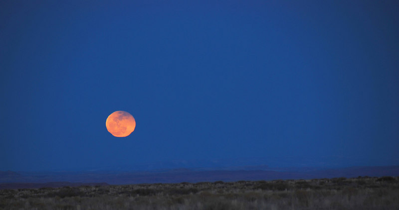 Full Moon Rising over the Canyonlands.  Shimmering in the desert heat.