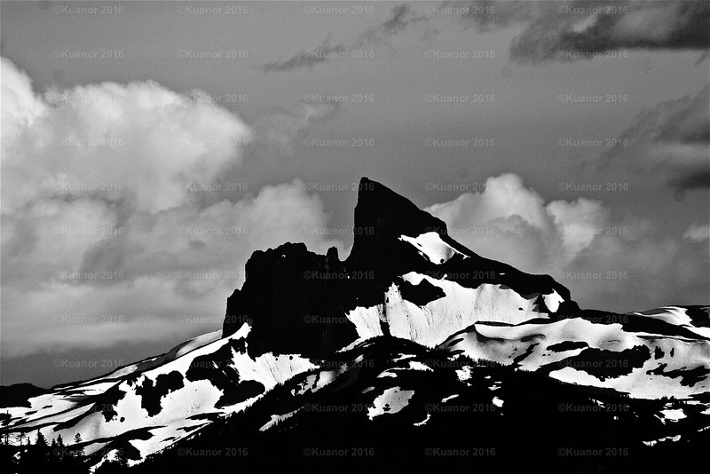 Black Tusk<br /> A dying mountain, for it is crumbling at a fantastic rate. Rocks break off nigh constantly to fall to the scree slopes below. The cracking sounds like gunshots; the resident ravens respond with indifference, fright and raucous outrage. In the winter, the viciously cold wind and snow accelerate the dying of the rock, and in the summer the heat expands the black rock to even further speed the mortality of this majestic mountain.