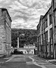 "Architectural merits - The warehouse on the right contrasts with the more ornate India Buildings to the left.   In the distance is Halifax station which would not look out of place in regency Bath.   The chimney rises above the former mackintoshes toffee factory ( now Nestle) where my grandmother once worked.  Beacon Hill dominates the background, itself once peppered with coal workings.   The white splash at the top is a grafitted ""Judd Wall""  these are large retaing walls behind which quarrying spoil was built up.   The whole  view is set-off by a mobile phone mast"