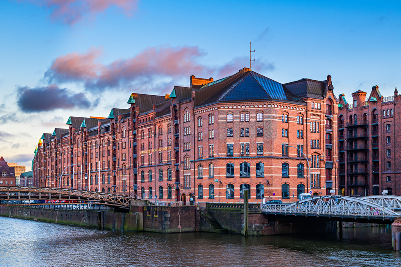 """Sunset and blue skies over the Hamburg Port Authority and Jungfernbrücke in Hamburg by Hafencity,"""