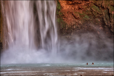 Two swimmers in the pool of Mooney Falls. Land of Supai Nation in the United States, Arizona.