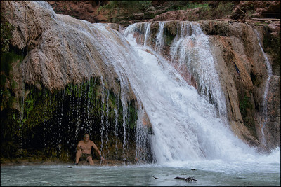 A swimmer cooling off in the grotto behind Beaver Falls. Land of Supai Nation in the United States, Arizona.