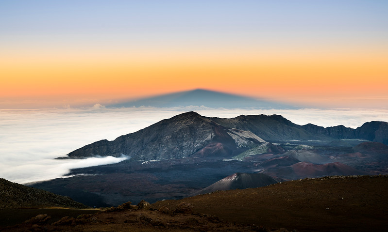 The shadow of the mountain at Haleakala National Park is projected in the distance at sunset.