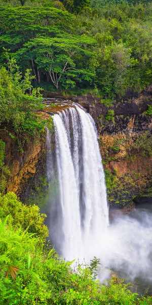 """Wailua Falls Vertical Panorama from Kauai"" This is the ""Fantasy Island"" waterfall from Kauai. I captured this from a different perspective - I climbed up on the wall which most people just view from and moved along until I could get thos<br /> e great blue and pink wildflowers just along the edges! I decided to try this as a vertical panorama for a nice tall wall for someones house. This is 5 shots captured vertically and stitched together to form the panorama. I love the details on the rocks at the top of the falls. Wailua Falls is an amazingly easy waterfall to get to so don't miss it! Lihue, Kauai, Wailua River State Park, Kauai County"