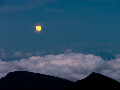 Moon rising at sunset on Pu'u'ula'ula Summit and Haleakala Observatories in Haleakala National Park, Maui, HI.