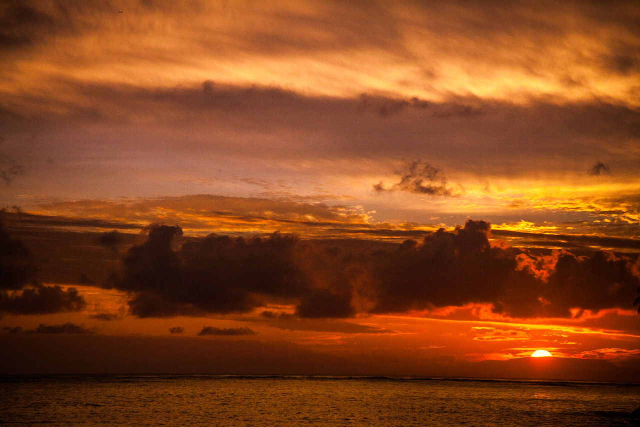 A beautiful orange sun rises over the calm ocean waters of the pacific ocean