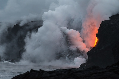 The molten lava explodes when it hits the water, sending off glowing bits of lava rock and lots of steam.
