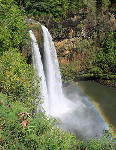 Wailua Falls in eastern Kauai with a rainbow in the mist at the base of the falls.