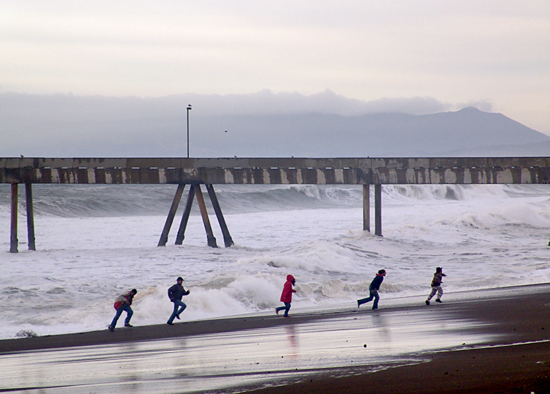 At least they were watching the waves! This group makes a mad dash for higher ground at the Pacifica Pier.