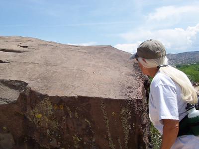 Our tour guide, Suzi, shows us an elaborately carved rock. The petroglyphs are so old they are nearly the same color as the surrounding stone and very hard to see now.
