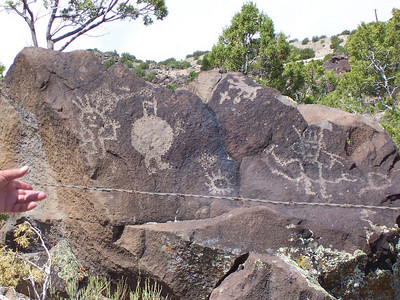 A stone with numerous petroglyphs.... a hunter with a shield, a detailed dog, a flute player and other figures.