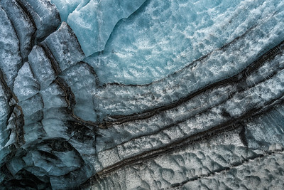 Like tree rings, the glacier has layers.  Blue is snow compressed to ice, black is ash from volcanic eruptions.