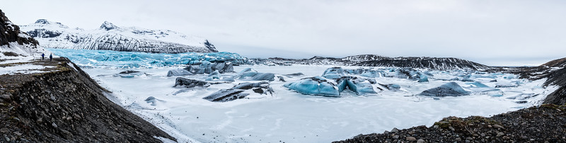 Pano with two group members and glacier at left, frozen lagoon center/right.