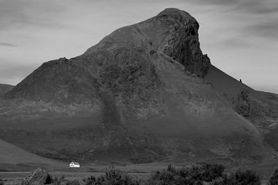 An Icelandic farmhouse dwarfed by a massive rock formation.