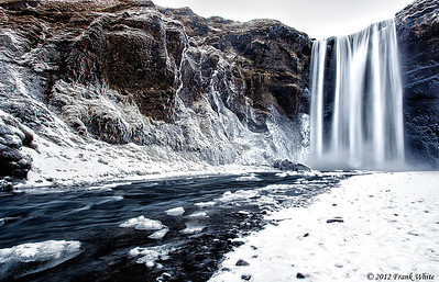 Skógafoss waterfall.  The mist from the waterfall has coated the surrounding rocks and canyon wall with frost and ice.