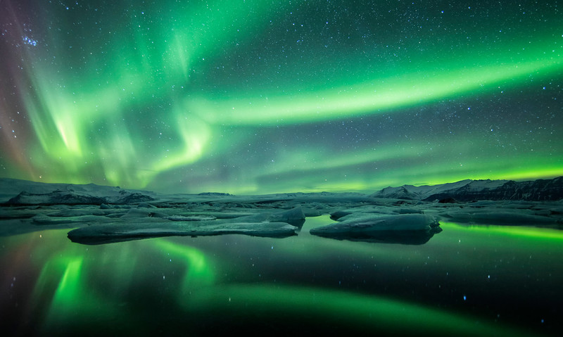 Northern light, aurora borealis, dancing across the sky above the glacier lagoon of Jokulsarlon, south Iceland.