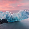 A giant chunk of blue ice sits on the shore of the Jokulsarlon Beach in southern Iceland.  A pastel sunset washes the scene.