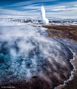 Overlooking one of the hot springs in the Geysir geothermal area, with Strokkur geyser erupting in the backgroud.
