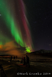 We photographed the aurora at Stokkur, which had just erupted in this photo; the vapor from the geyser drifted off to the left, catching the orange light from the restaurant nearby.