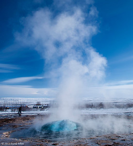 "Strokkur geyser, just at the start of the eruption. It is a ""pool geyser"" and the erruption begins suddenly as a large bubble of gas comes up from the crevase under the geyser pool, pushing it upward. The eruptions happen every 10-12 minutes."