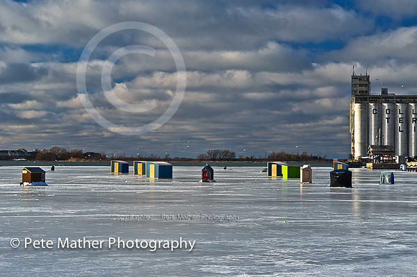 Collingwood fisherman on the frozen harbour, using huts to fish from. There was a burst of sunshine and used the polar filter. What a cloud bank with sea gulls flying around.