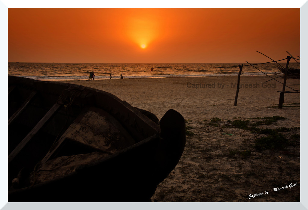 Essentially Goa - a fishing boat lies in wait for its owner, as tourists enjoy the waters @ Colva Beach