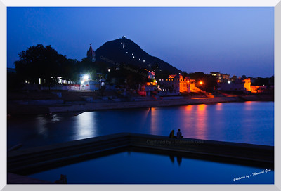 A pilgrim couple spends a quite moment in the holy city of Pushkar, Rajasthan after sun down