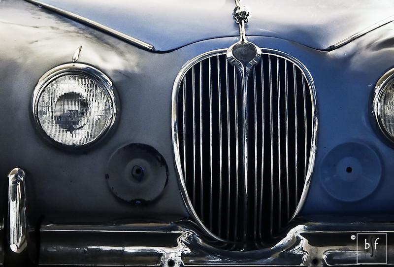 An old light blue 1961 Jaguar MK2 parked near the pool.