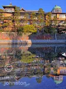 """Koi [carp] in the Matsukawa River as it passes beneath the old Japanese Inn """"Tokaikan"""" in the city of Ito, Shizuoka Prefecture, Japan.  Tokaikan 東海館 """"Eastern Sea Inn"""", is wooden structure built in 1913 as a sort of community facility for enjoying Ito's hot springs.  The three-story building features extraordinary craftsmanship in cedar and Japanese cypress.  The Matsukawa 松川 """"Pine River"""" runs from the Matsukawako 松川湖 """"Pine River Lake"""", eastward through the city of Ito, into the Pacific Ocean."""