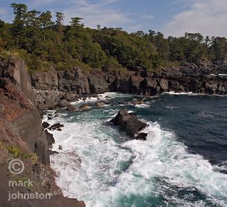Waves crash against volcanic rock on the rugged coastline of the Izu Peninsula, Shizuoka Prefecture, Japan.