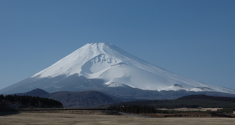 "The Fuji Safari Park lies to the SE of the mountain. From afar, the ""skirts"" rise gracefully to the peak, but in fact the 1705 eruption created is a large caldera on this side. Just outside the northern parking area of the Park lies a huge open field with this unobstructed view of the southern face."