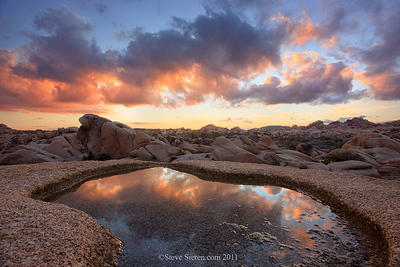 "Magnificent Desert Sunset reflection of colorful clouds at Joshua Tree National Park.  Boulders and rocks in the distance.  Editing a few photos from the Joshua Tree workshop over the weekend. We had a small group and I had one cancellation due to the weather. A little bit of rain in the desert wouldn't hurt anyone, the dramatic weather created a lot of unusual opportunities for us to photograph such as fog in the high desert, dramatic sunsets / sunrises and little pockets of water in many different places. These little pools are also known as ""tanks"" if they get big enough. Don't run from the weather that's only bring goodness with it! The next one - http://bit.ly/smPSZM"